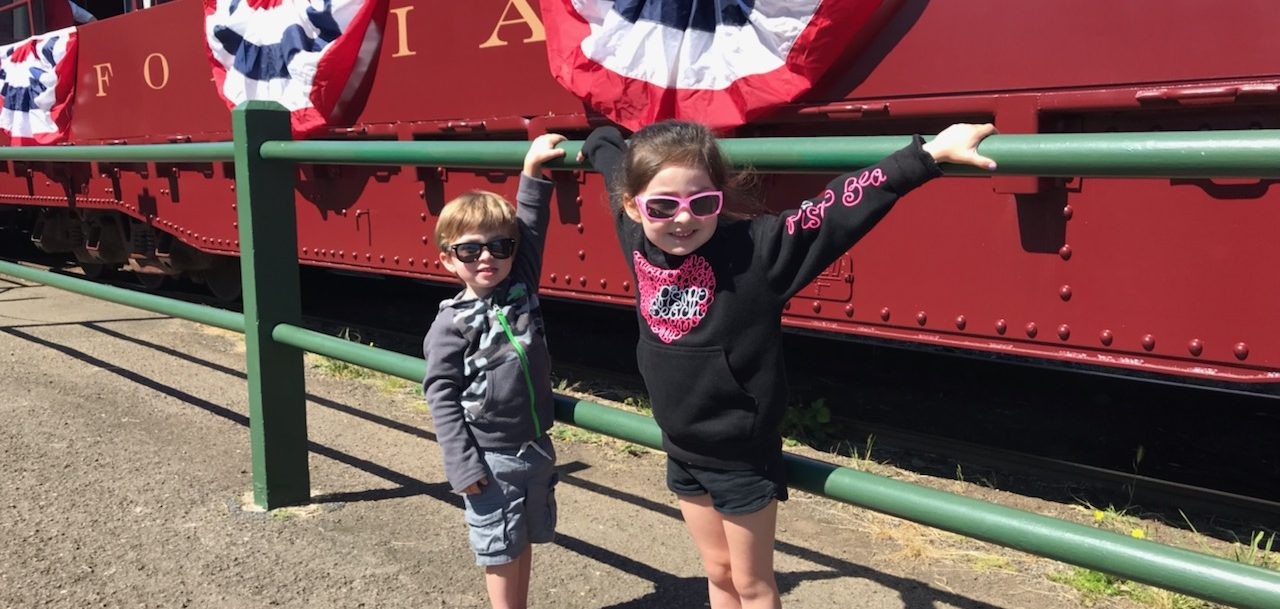 two kids standing near skunk train in mendocino