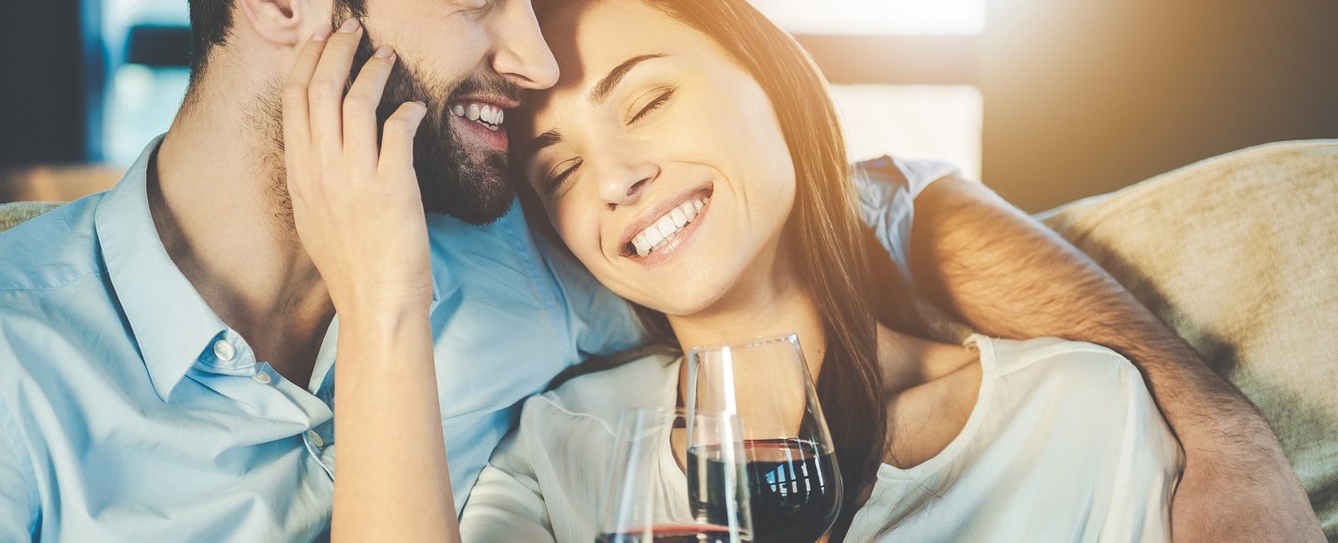Man and woman each holding glass of red wine